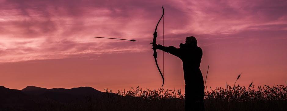 Zdjęcie: łucznik strzelający z łuku na tle zachodu słońca