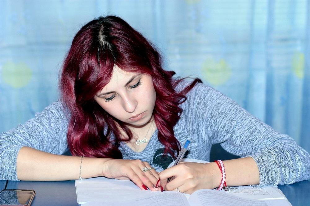 Zdjęcie: kobieta pisząca w zeszycie (doradca inwestycyjny 2 etap)