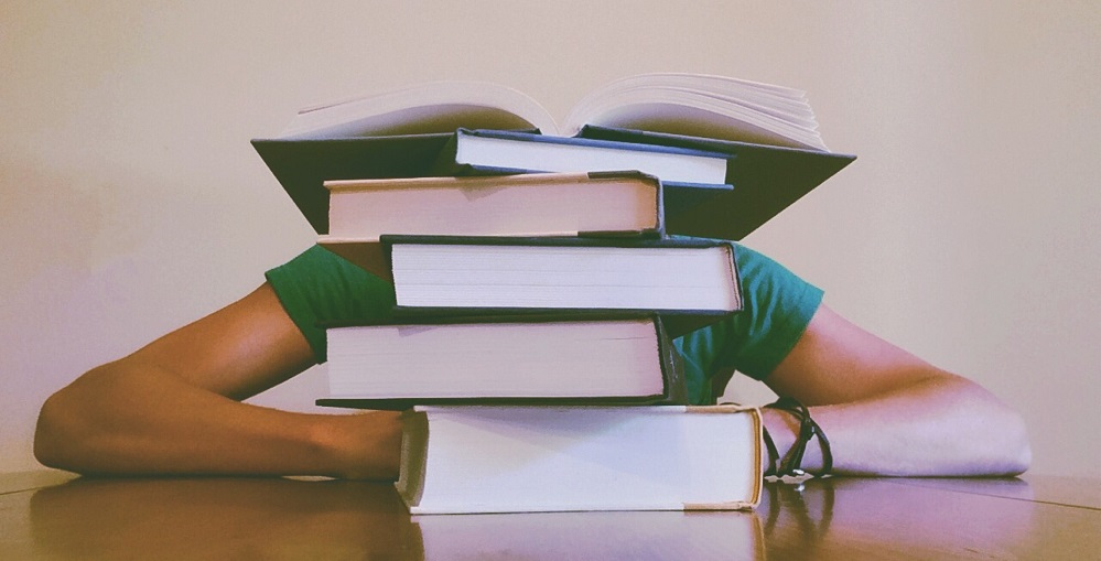 Zdjęcie: osoba za stertą książek