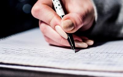Zdjęcie: osoba pisząca na kartce. Doradca inwestycyjny 2 etap.