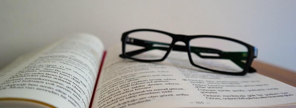 Zdjęcie: okulary leżące na rozłożone (3 etap egzaminu na doradcę inwestycyjnego)
