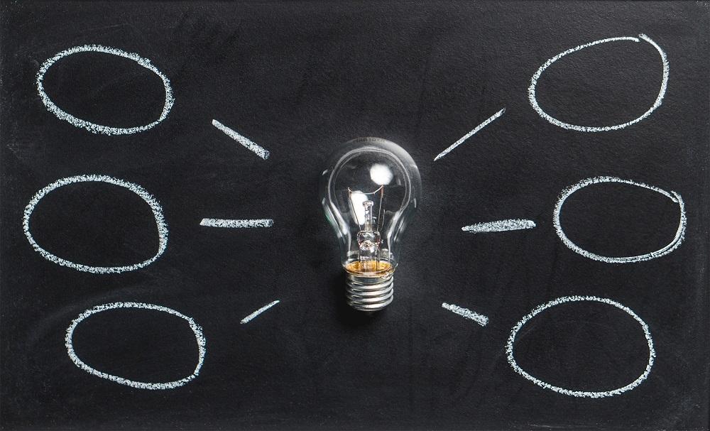 Zdjęcie: żarówka na tle tablicy (doradca inwestycyjny 3 etap)