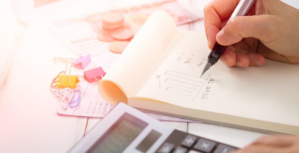 Zadania z finansów z rozwiązaniami - zdjęcie: zeszyt i pisząca osoba